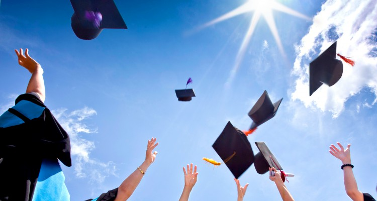 Students-with-congratulations-throwing-graduation-hats-in-the-air-celebrating