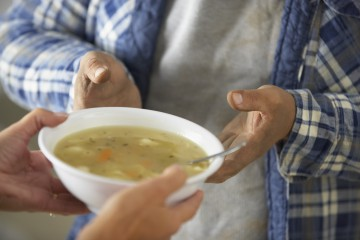 Hands of Homeless Man Receiving Bowl of Soup