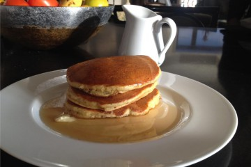pancakes and syrup on a white plate.