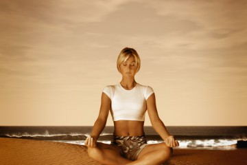 Woman Meditating at the Beach